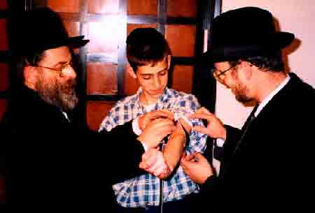 Bar mitzvah boy learning how to put on his new tefillin