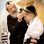 rabbi teaching a bar mitzvah boy how to put on tefillin, teffilin, phylacteries